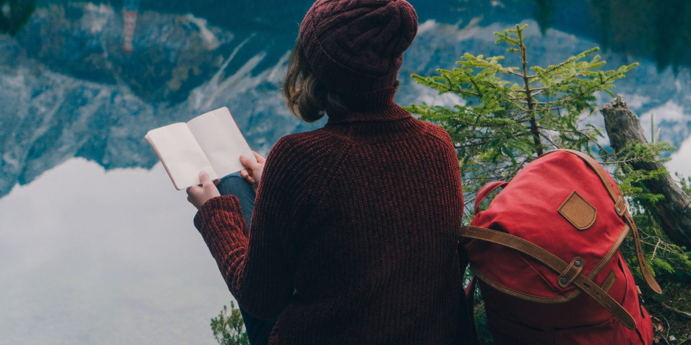 Young woman reading notebook on the background of scenic view of Eibsee lake in Bavarian Alps, Germany