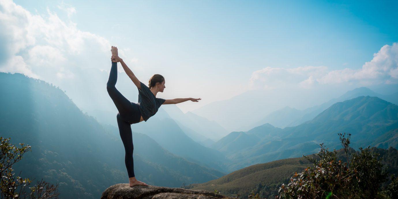 Woman training yoga at sunrise, mountains on background