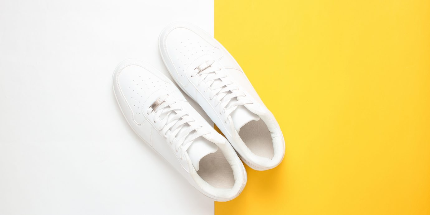 Fashionable white sneakers on a colored pastel background