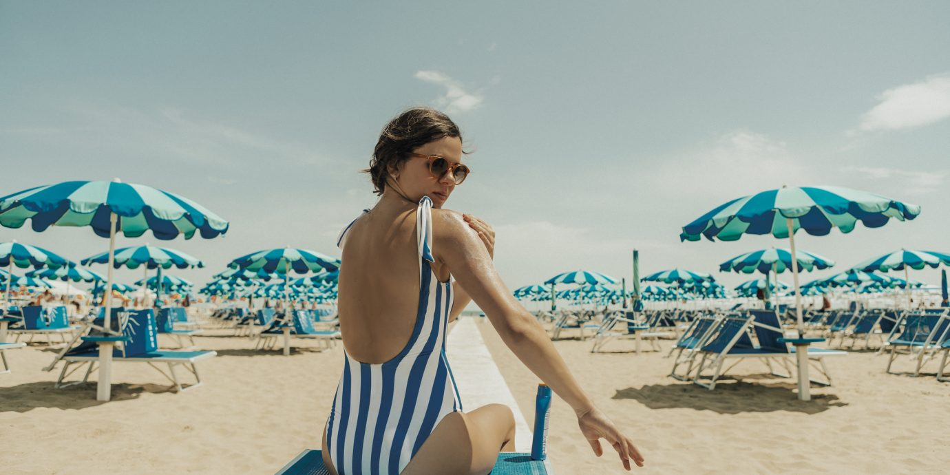 Young woman putting sunscreeen at iRimini, Italy