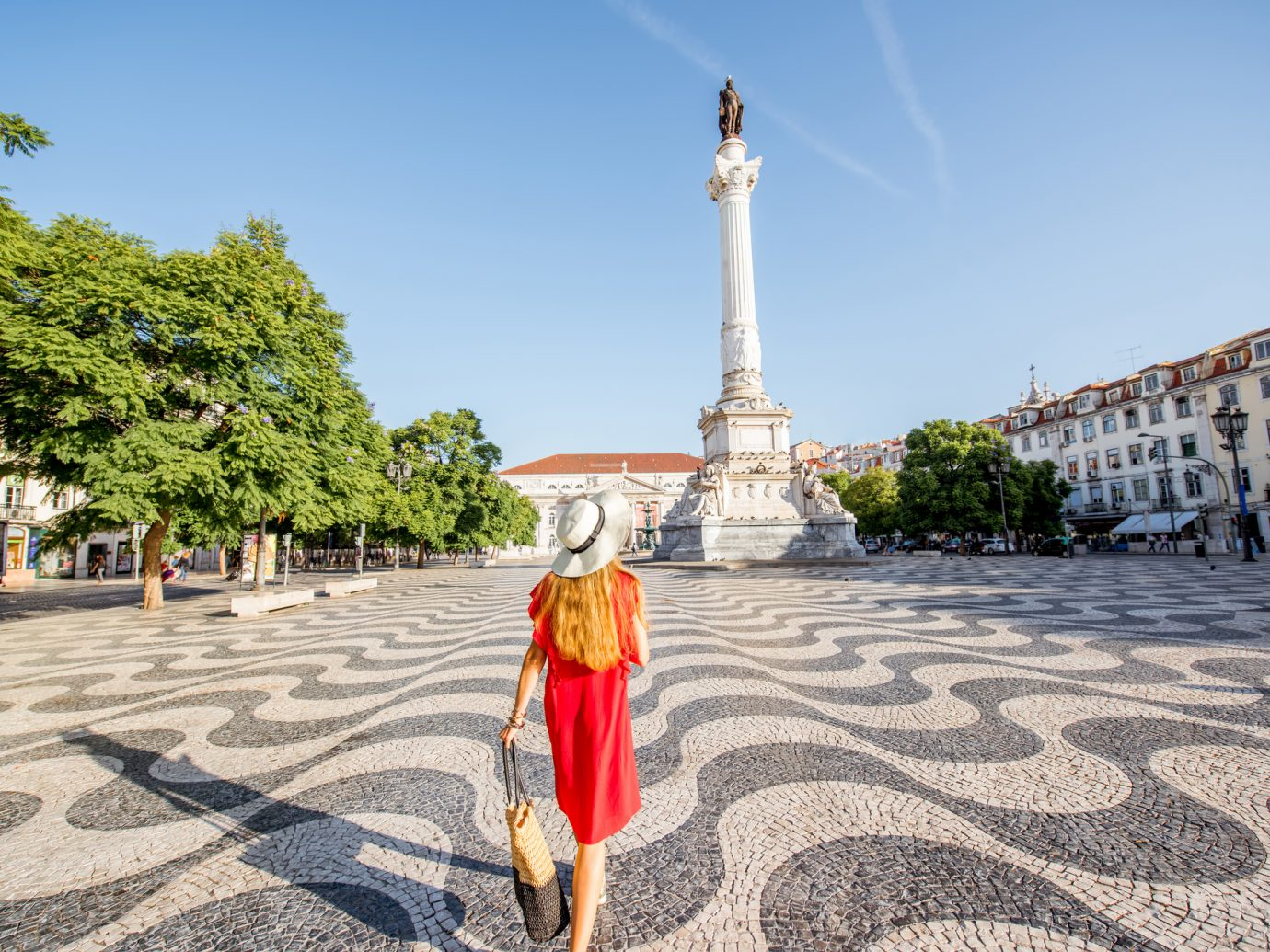 Young woman tourist walking on the Rossio square with Pedro statue during the morning light in Lisbon city, Portugal