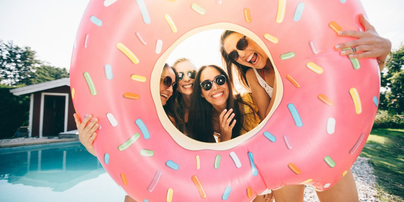 girls weekend getaway, Four girls holding a pink pool inflatable around their faces like a frame while laughing together and standing outdoors next to a pool