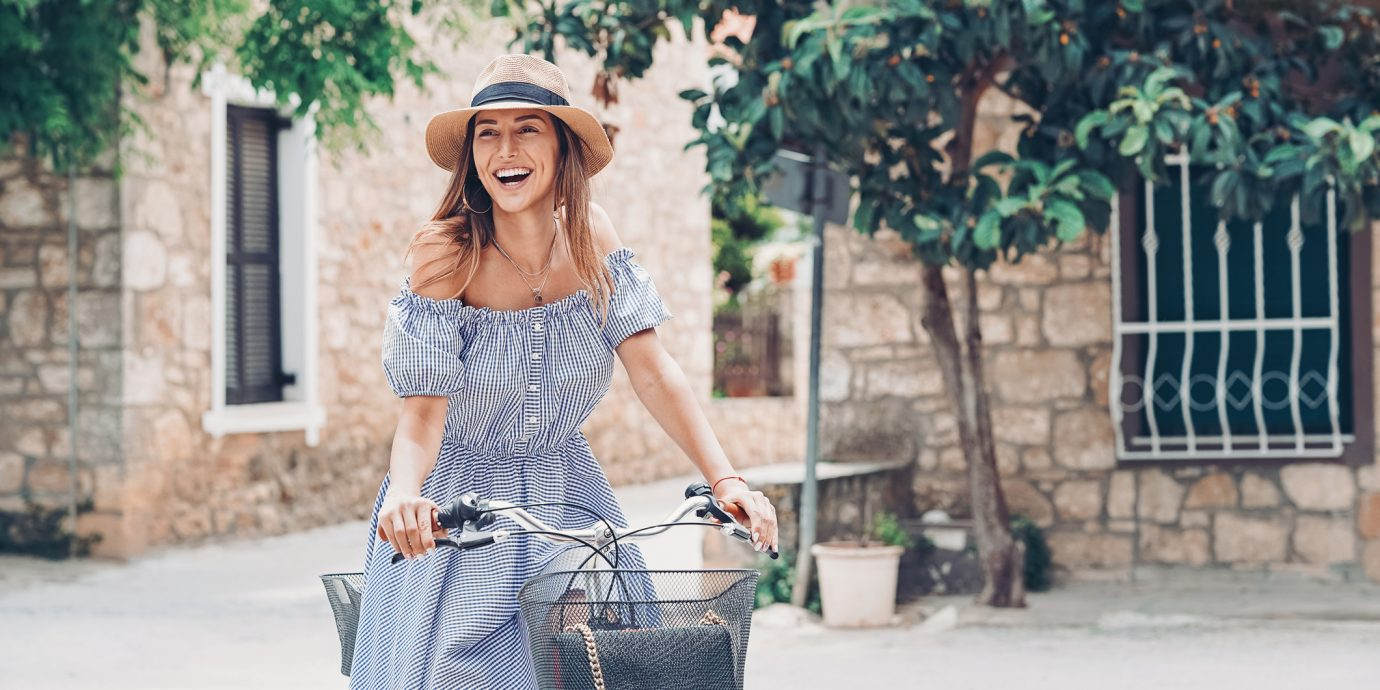 Smiling young woman riding a bike, Summer dresses under $150