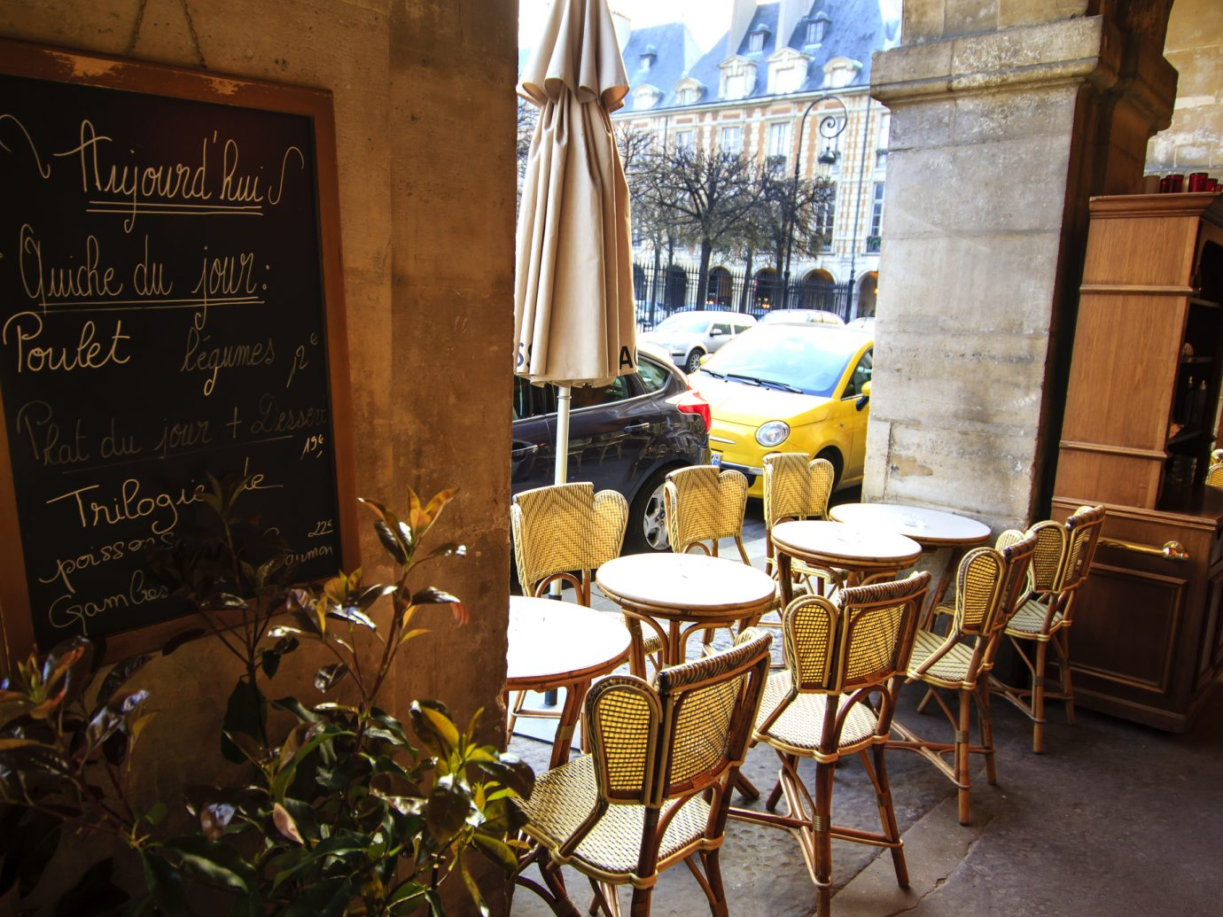 Paris, Place de Vosges - cafe under arches with it's aligned tables and menu board on the wall.
