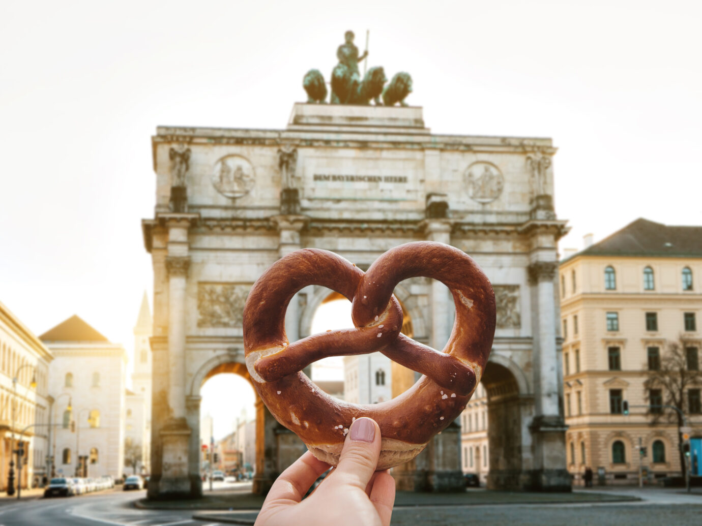 Person holding a pretzel in front of Victory Gate triumphal arch Siegestor in Munich. Germany
