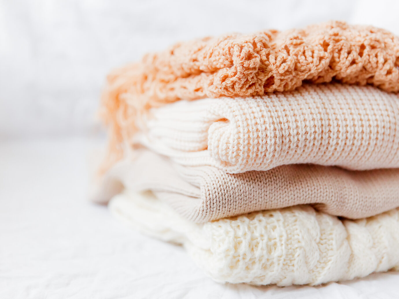 ThredUp Pile of beige woolen clothes on a white background. Warm knitted sweaters