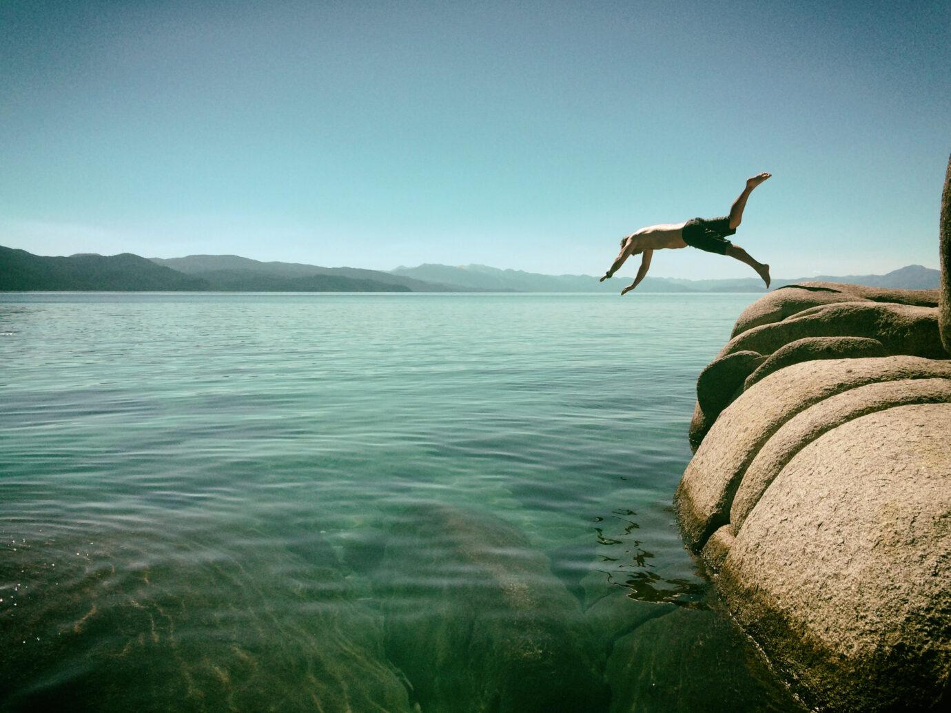 Man diving off rocks into Lake Tahoe