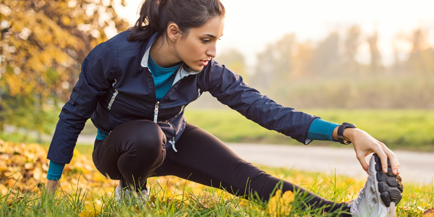 Young woman exercising at park during sunset. Beautiful athletic woman doing her stretches in the park in autumn. Sporty woman stretching after a good workout session outdoor.