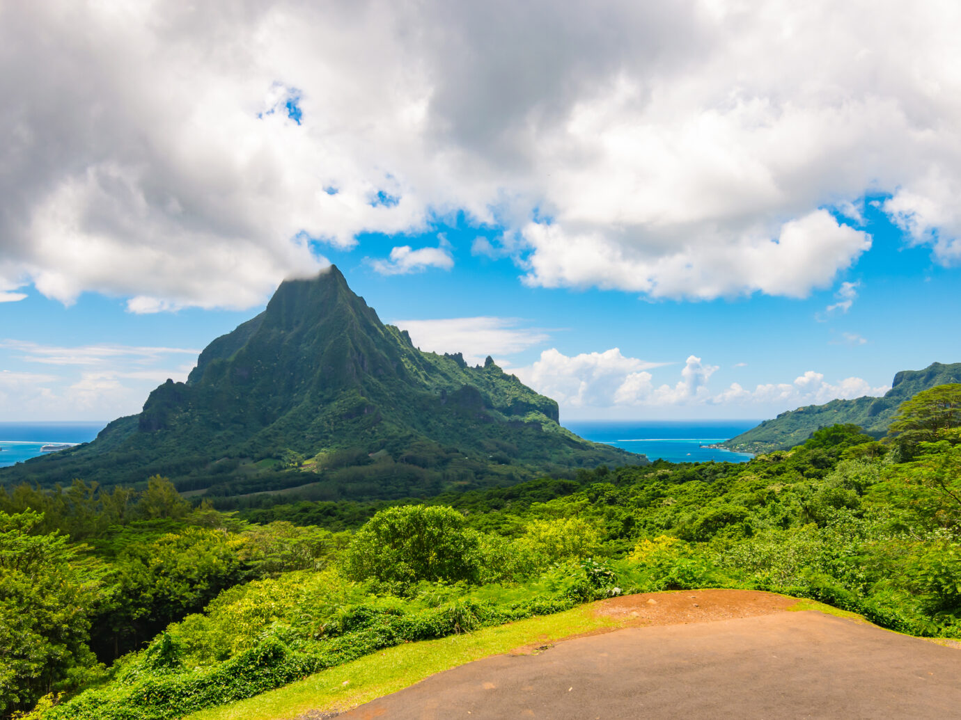 Mountain with two oceans on the side. Vewpoint with mountain landscape of Moorea, French Polynesia. Blue sky with clouds. Cruise destination.