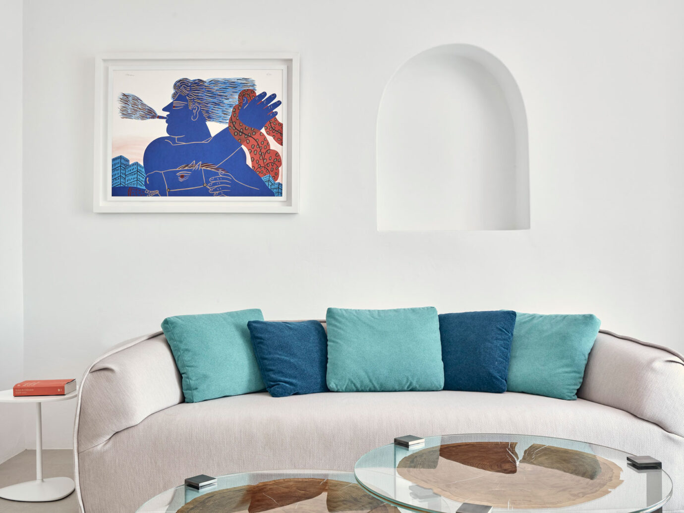 white living room with blue accents at the Myconian Ambassador Hotel, Greece