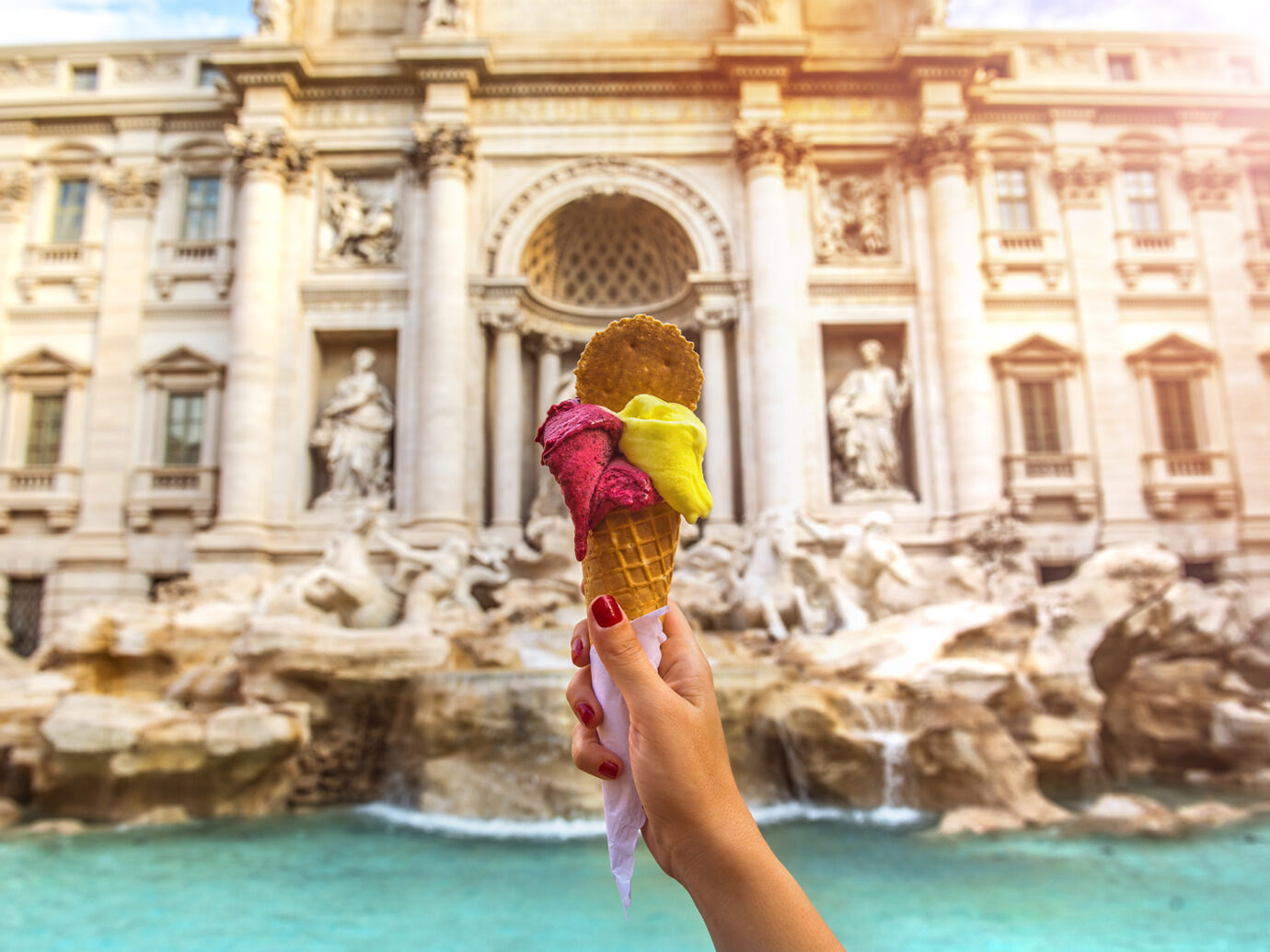 Hand holding colorful gelato in front of famous iconic Trevi Fountain at Rome, Italy.