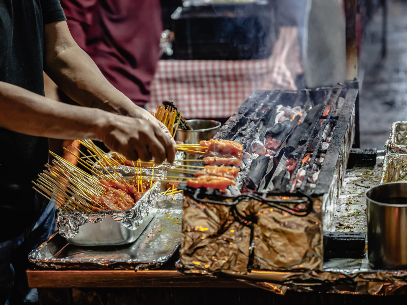 A grill and skewer expert at work on Lau Pa Sat hawker center's famous Satay Street. Singapore.