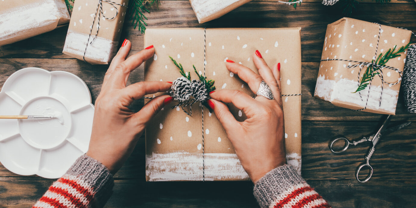 Editors favorite gifts to give and get, Woman´s hands wrapping Christmas presents on brown paper decorated with painted snow, fir branches and pinecones on a rustic wooden board. Top view