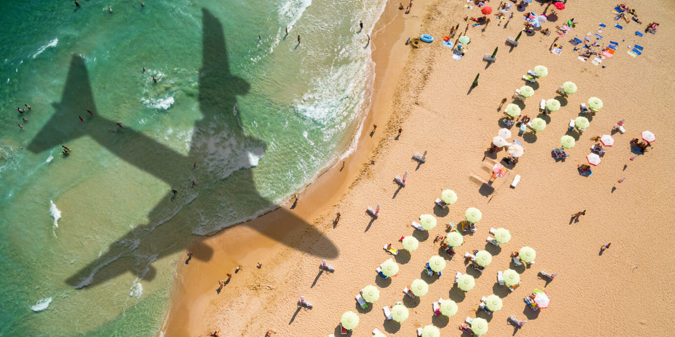 Aerial view airplane shadow and beach with umbrellas