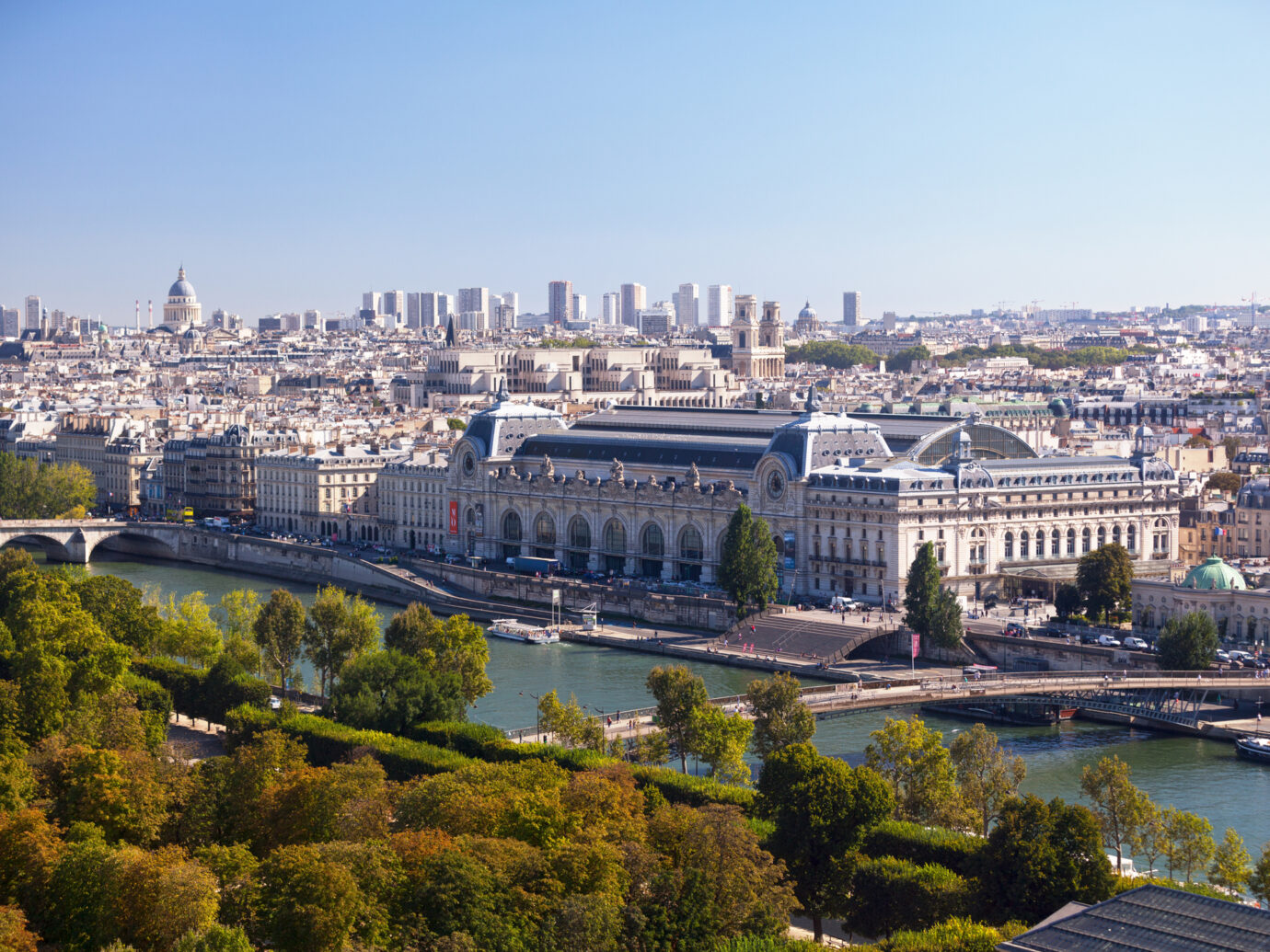 Aerial view of Paris centered on the Musée d'Orsay but also including the Seine River, the Jardin des Tuileries, the Musée national de la Légion d'honneur et des ordres de chevalerie, the Université Paris Descartes, the Église Saint-Sulpice, the Palais du Luxembourg and the Panthéon de la Sorbonne.