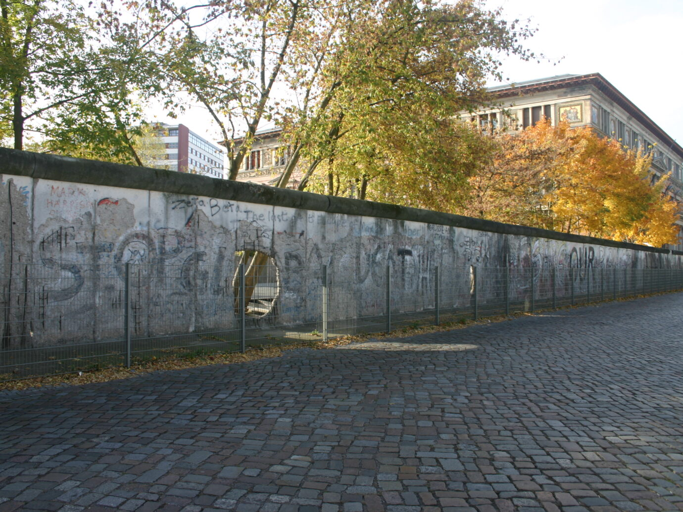A fenced off section of the Berlin Wall along a cobblestone road.