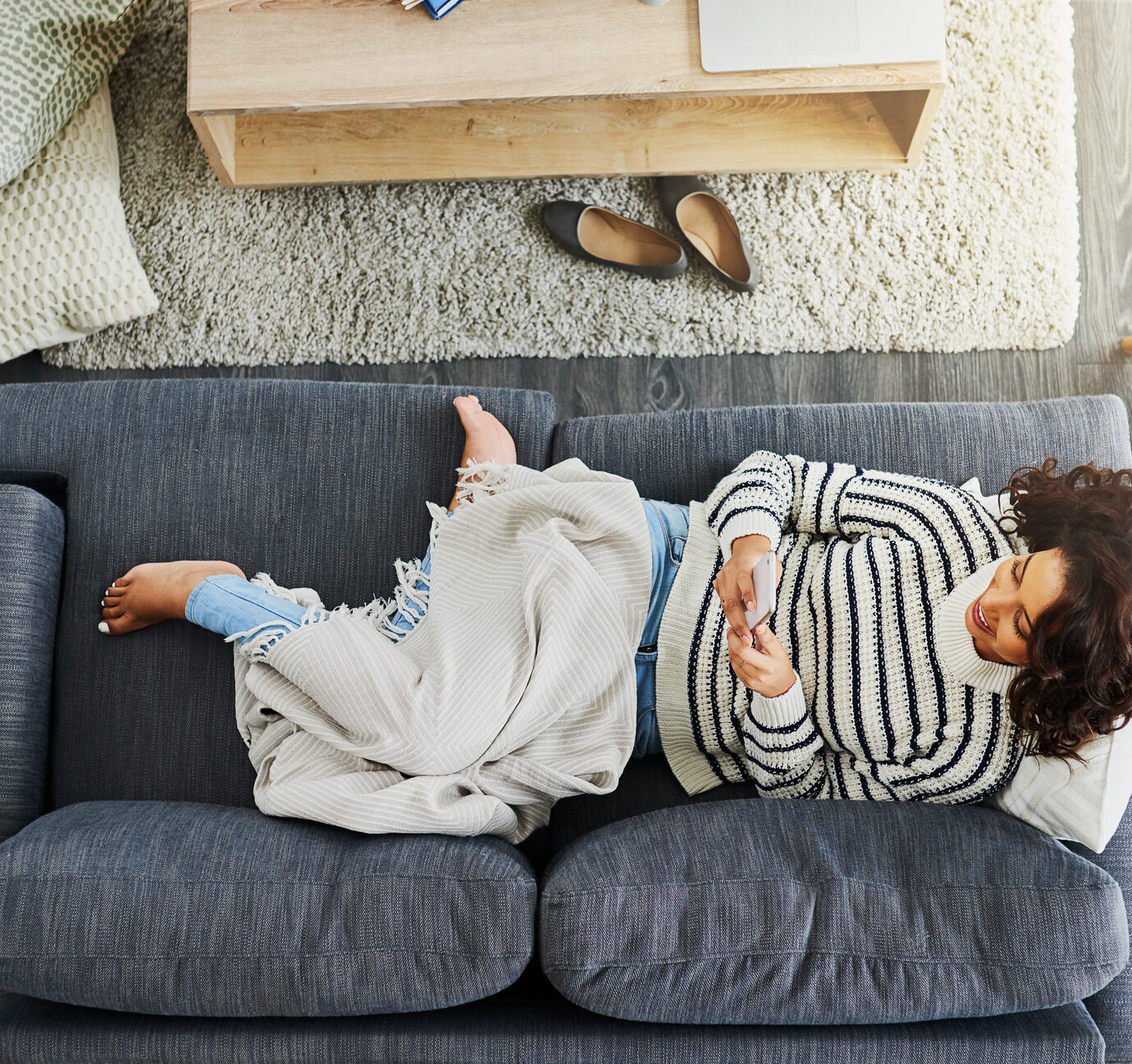 High angle shot of an attractive young woman using her cellphone while relaxing on a couch at home