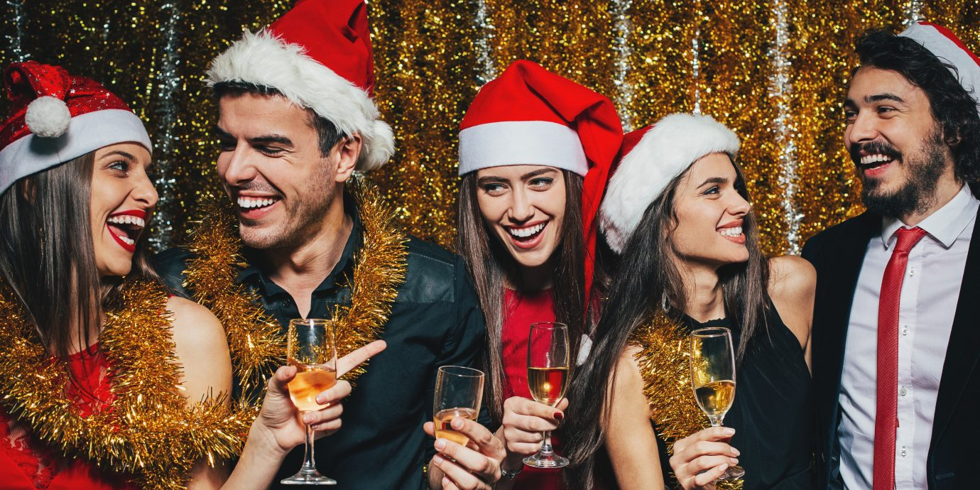 Group of cheerful people with champagne glasses wearing Santa hats on Christmas celebration.