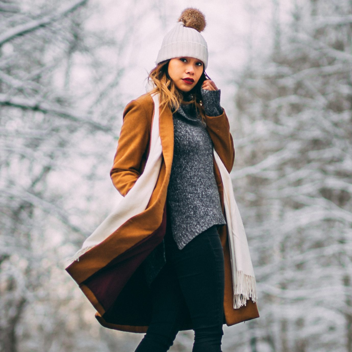 woman on a snowy street with a tan wool winter coat