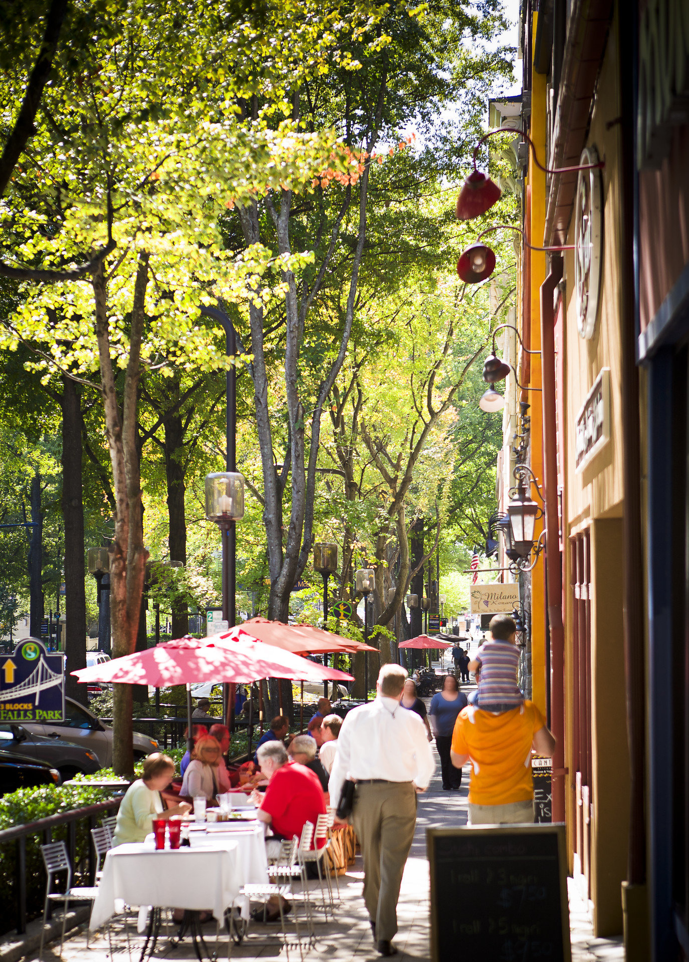 Buildings charming city streets cozy Greenery homey outdoor dining Outdoors people quaint shopping Shops streets tables trees Trip Ideas tree outdoor street neighbourhood season flower spring autumn