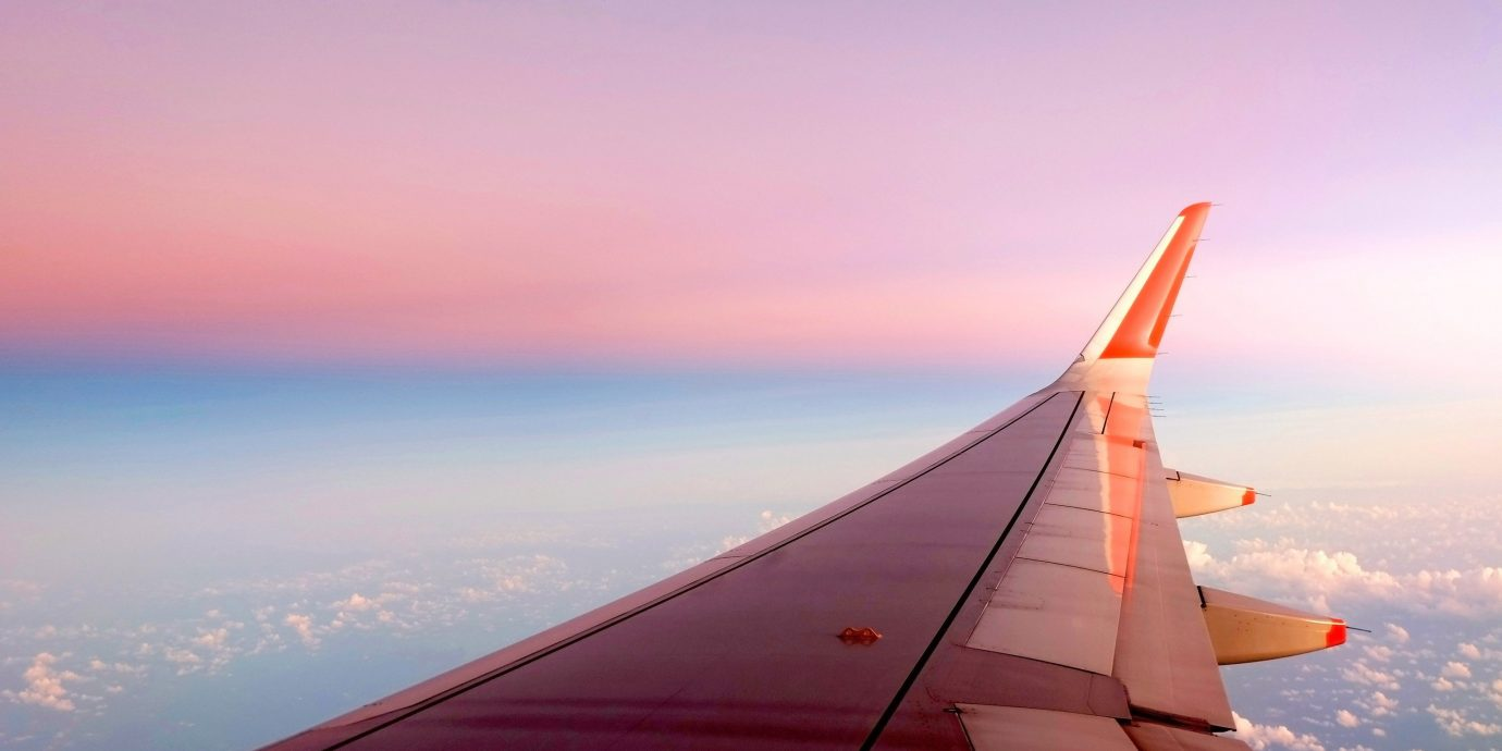 Travel Tips sky outdoor water plane airplane horizon aircraft airline flight atmosphere of earth vehicle sunrise Sea Sunset aviation airliner orange narrow body aircraft wing gliding dusk dawn wind distance