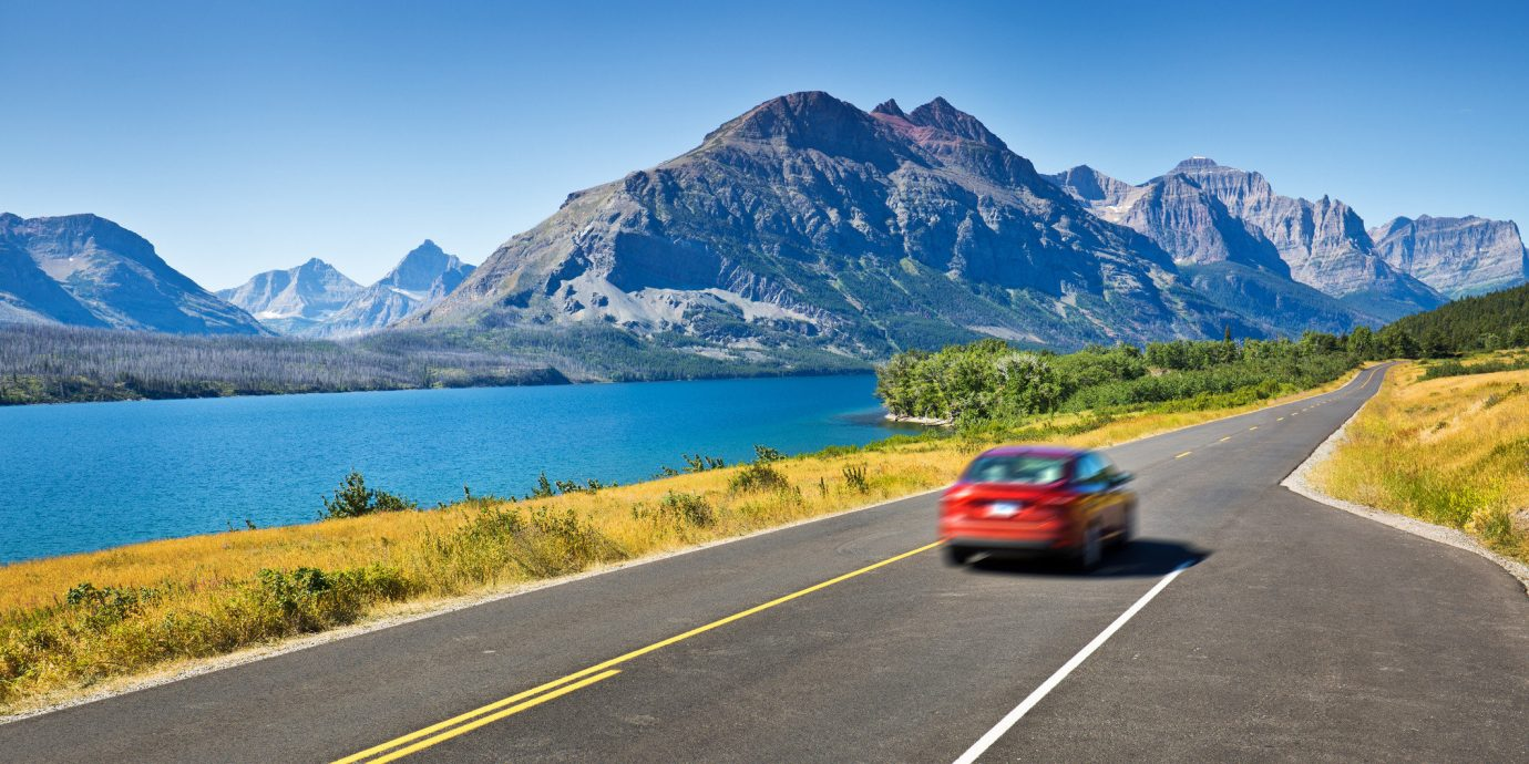 Road Trips Travel Tips mountain sky road outdoor grass mountainous landforms mountain range way scene car highway roadway road trip mountain pass vehicle alps infrastructure Lake controlled access highway fjord driving reservoir traveling highland