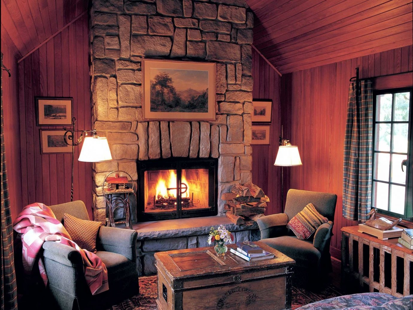 All-inclusive Fireplace Hotels Lakes + Rivers Living Lodge Resort Romance Waterfront room indoor sofa fire floor living room ceiling window house home cottage estate interior design hearth furniture wood farmhouse stone