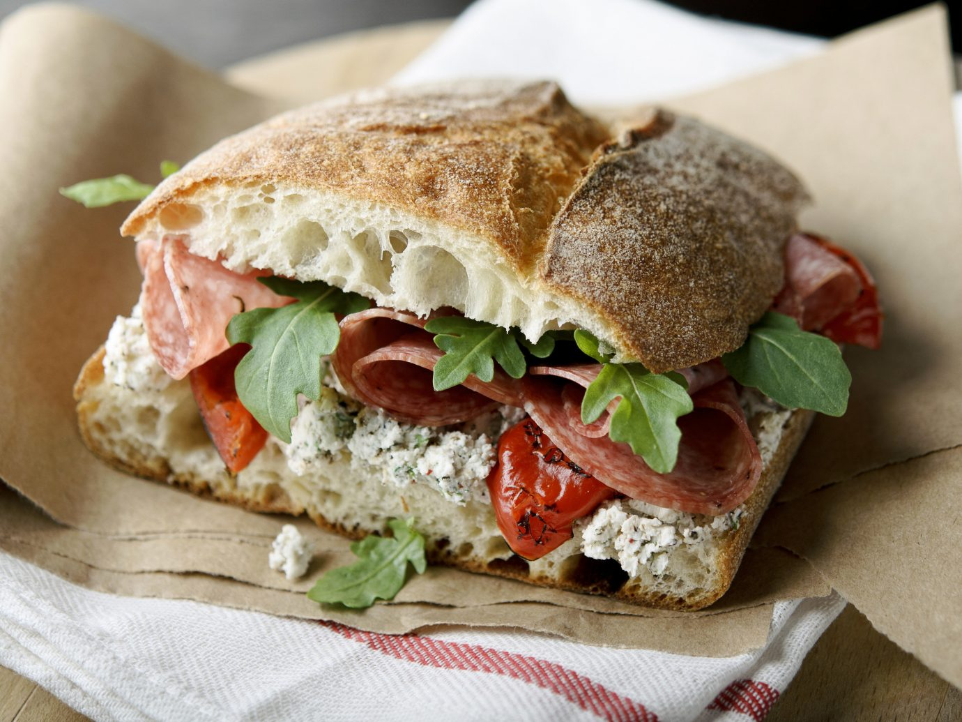 Food + Drink food sandwich paper snack food dish muffuletta blt submarine sandwich cuisine produce meat meal lunch ciabatta half