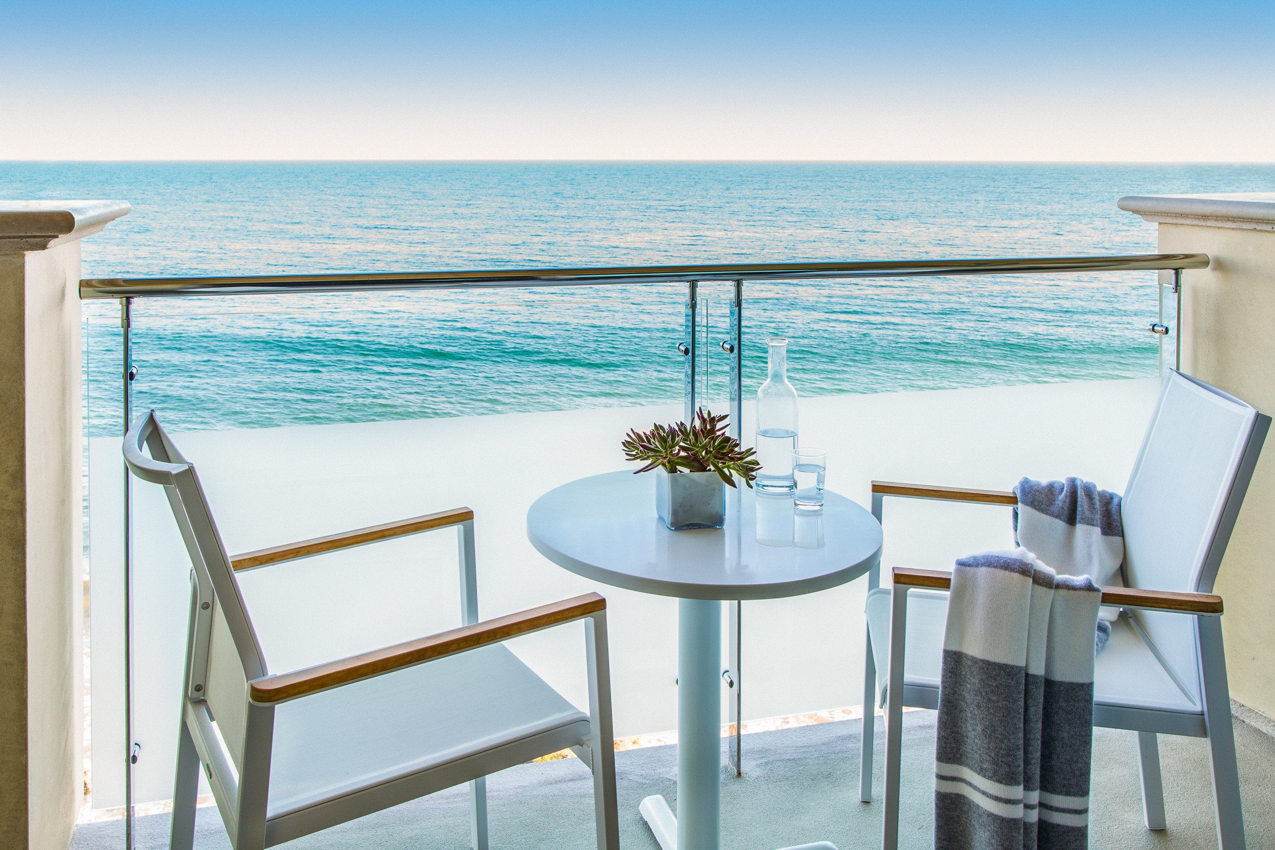 Arts + Culture Hotels Jetsetter Guides shopping Travel Trends Trip Ideas water sky chair body of water Sea outdoor table Ocean vacation furniture real estate Balcony overlooking shore Beach house Deck