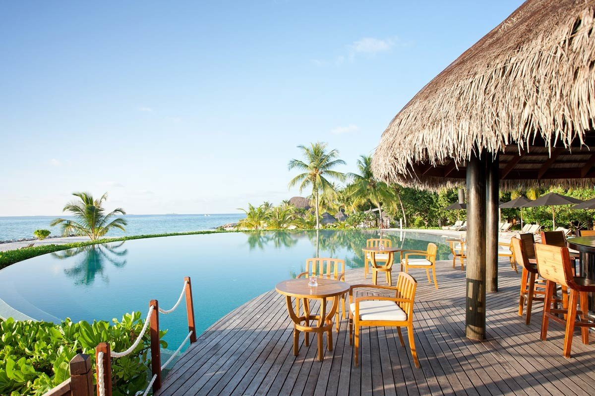 All-Inclusive Resorts Hotels sky outdoor water Resort property chair leisure vacation real estate swimming pool estate wooden Villa tourism eco hotel tropics resort town palm tree outdoor structure Lagoon arecales caribbean cottage furniture several