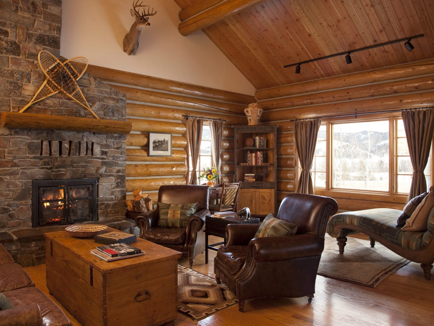 Glamping Hotels Montana Outdoors + Adventure Trip Ideas indoor Living room floor Fireplace property window living room estate home fire log cabin house furniture cottage hardwood ceiling wood farmhouse interior design real estate wood flooring stone