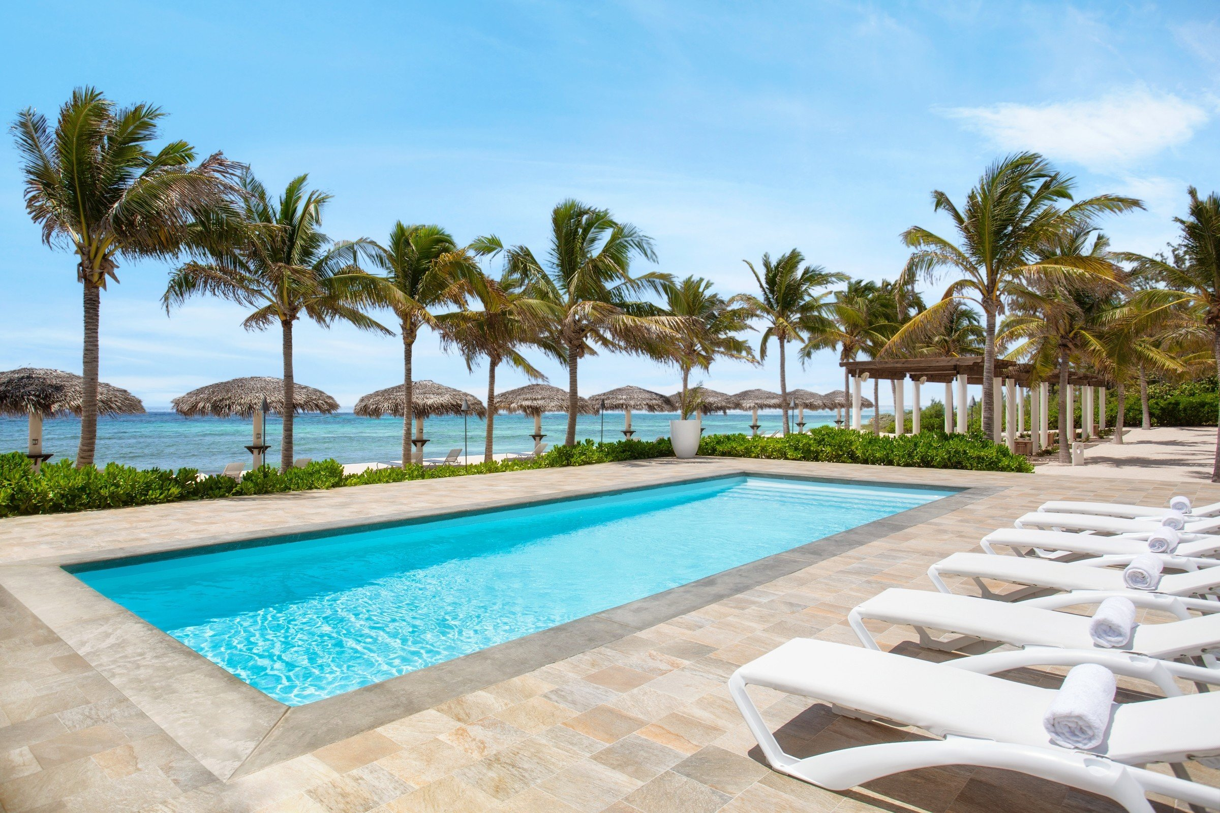 Hotels outdoor tree sky Beach Pool ground Resort palm swimming pool property chair building leisure lawn caribbean estate vacation lined Villa condominium real estate swimming sandy Deck shade