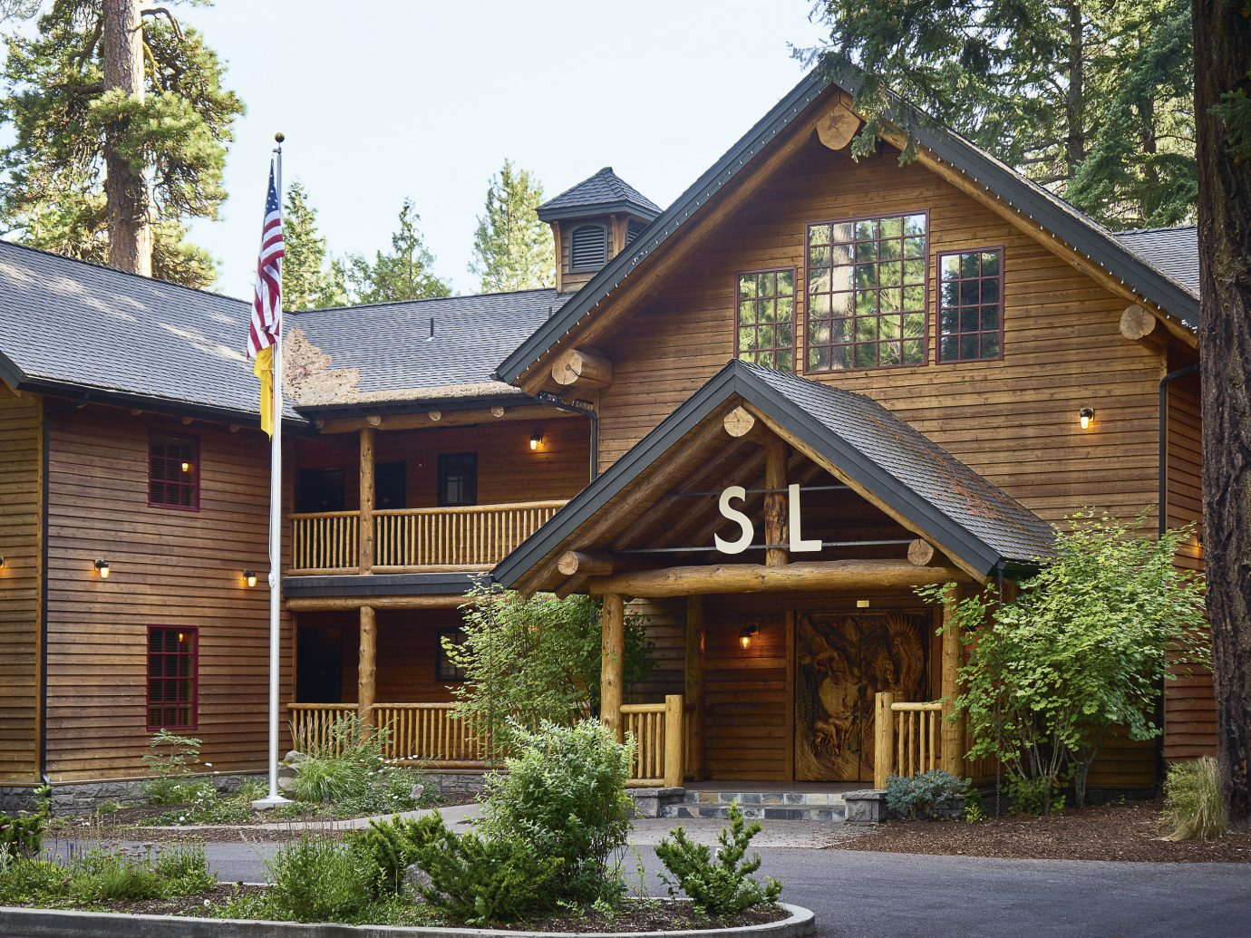 Boutique Hotels Fall Travel Hotels Outdoors + Adventure tree outdoor sky building house home property estate log cabin residential area cottage siding real estate residential facade old farmhouse roof Resort Garden Town bushes stone