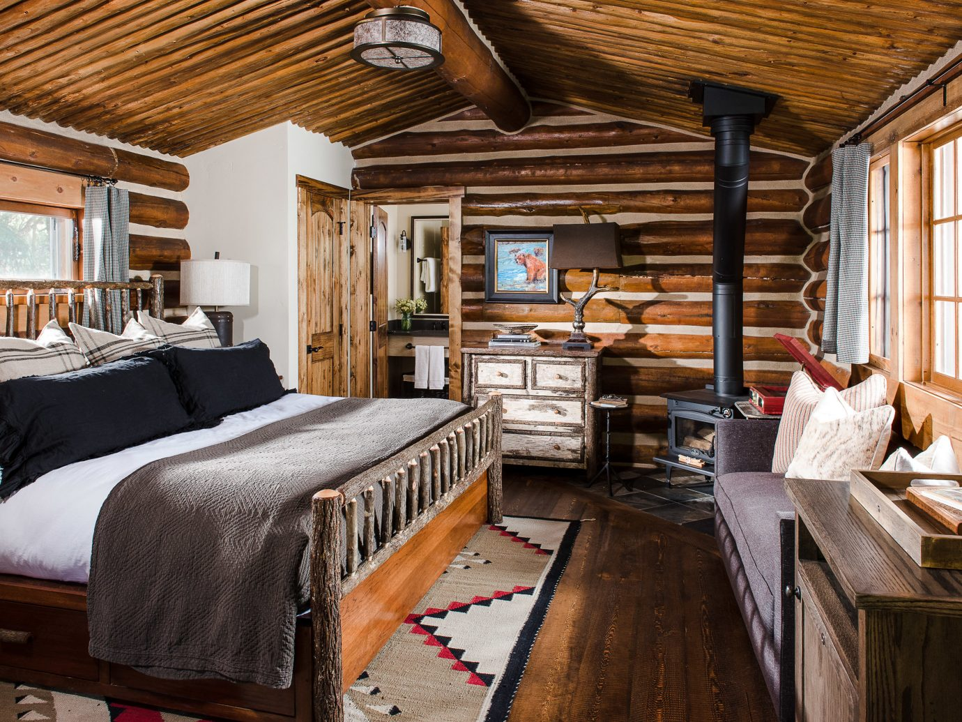 Glamping Hotels Montana Outdoors + Adventure Trip Ideas indoor floor room bed ceiling Bedroom window wood interior design real estate beam living room log cabin furniture bed frame