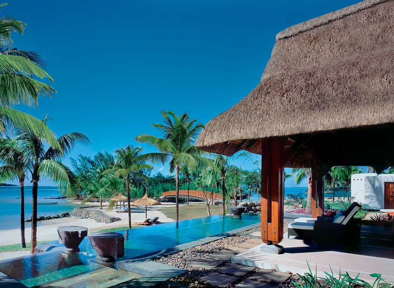 Hotels tree outdoor umbrella leisure building Resort property vacation caribbean swimming pool Beach tourism Pool estate Sea arecales Villa Lagoon palm furniture area shade several