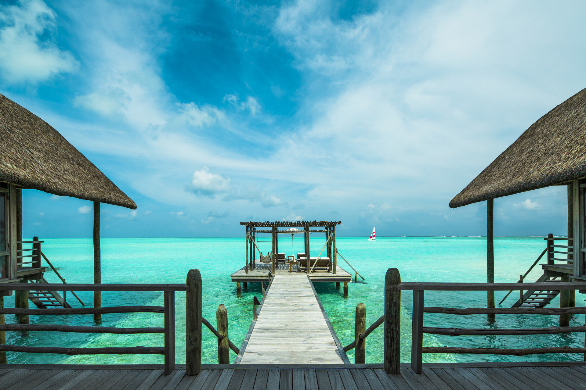 Hotels water outdoor pier sky chair scene umbrella blue Sea Ocean vacation Beach cloud Pool Coast caribbean bay Island empty swimming lined shade