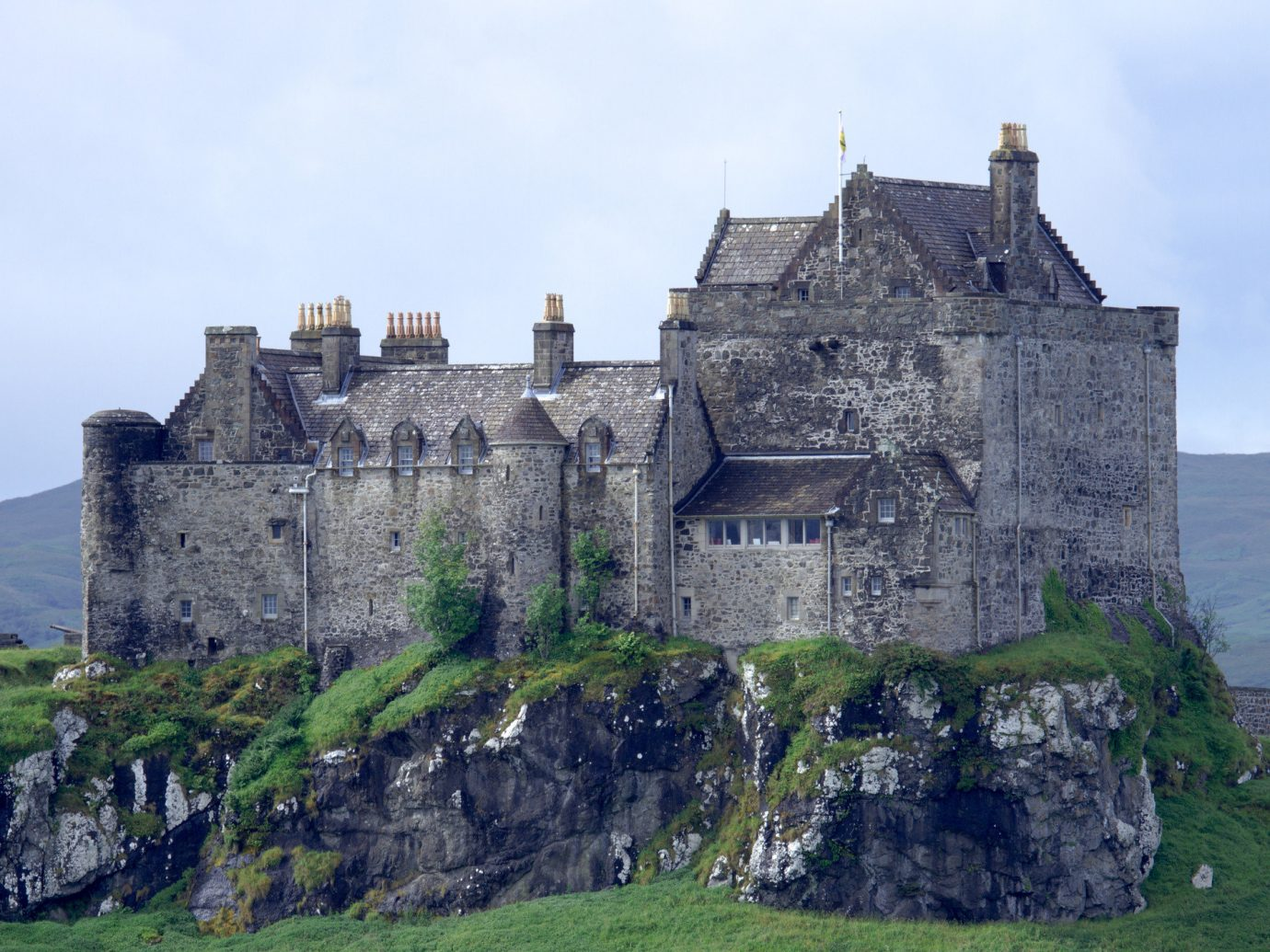 Landmarks Offbeat building grass sky outdoor castle rock château medieval architecture fortification highland stone old national trust for places of historic interest or natural beauty middle ages historic site Ruins stately home turret citadelle tours history grassy pasture hillside