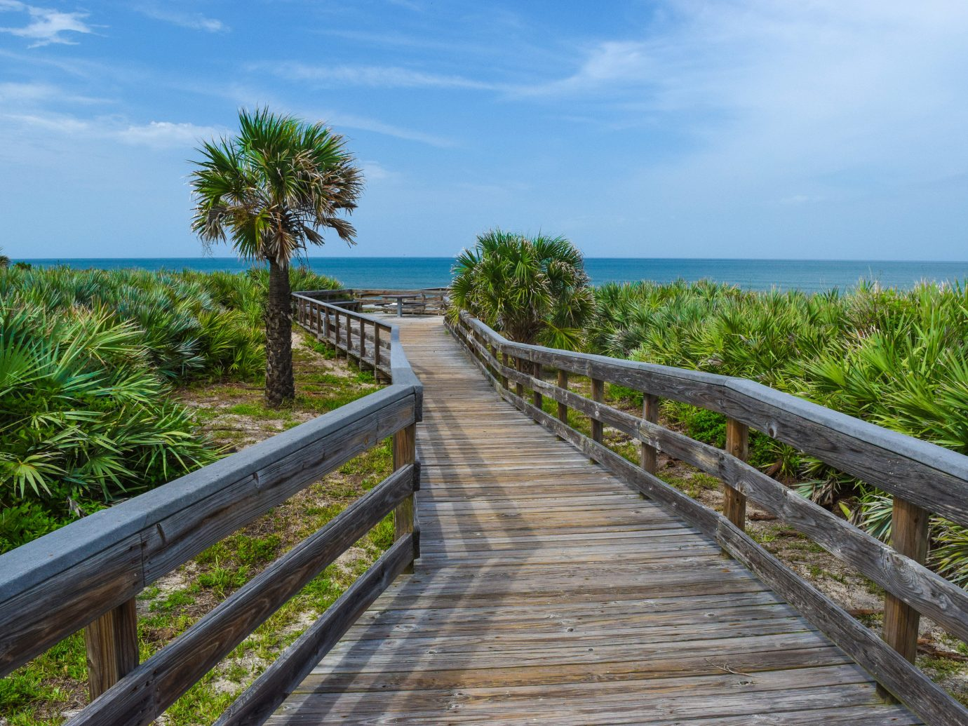 Road Trips Trip Ideas sky outdoor bench wooden boardwalk walkway vegetation plant Sea Coast Ocean arecales tree shore palm tree Beach tropics grass real estate water railing landscape vacation cloud overlooking