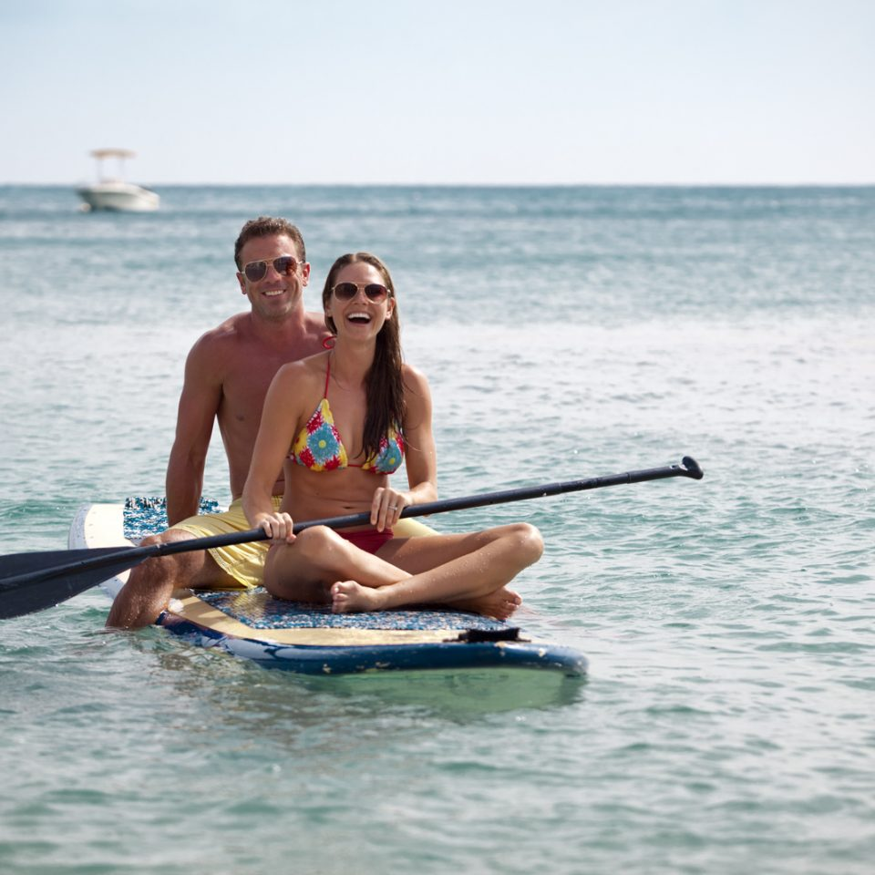 Man and woman sitting and laughing on paddle board in the ocean