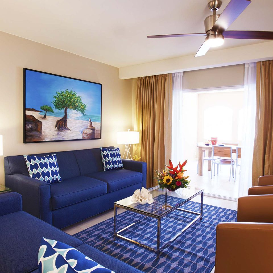 Living room interior with dark ocean blue furniture and accents with slight view of balcony