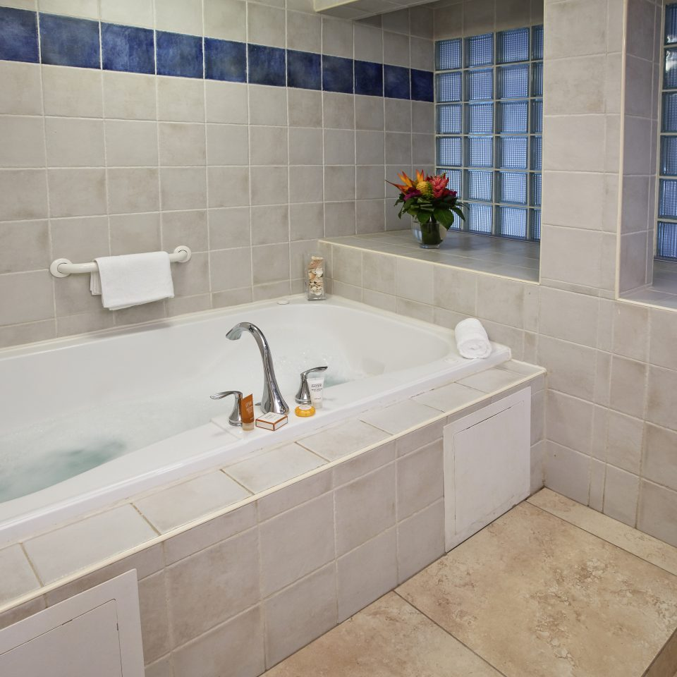Half filled bathtub with tiled wall