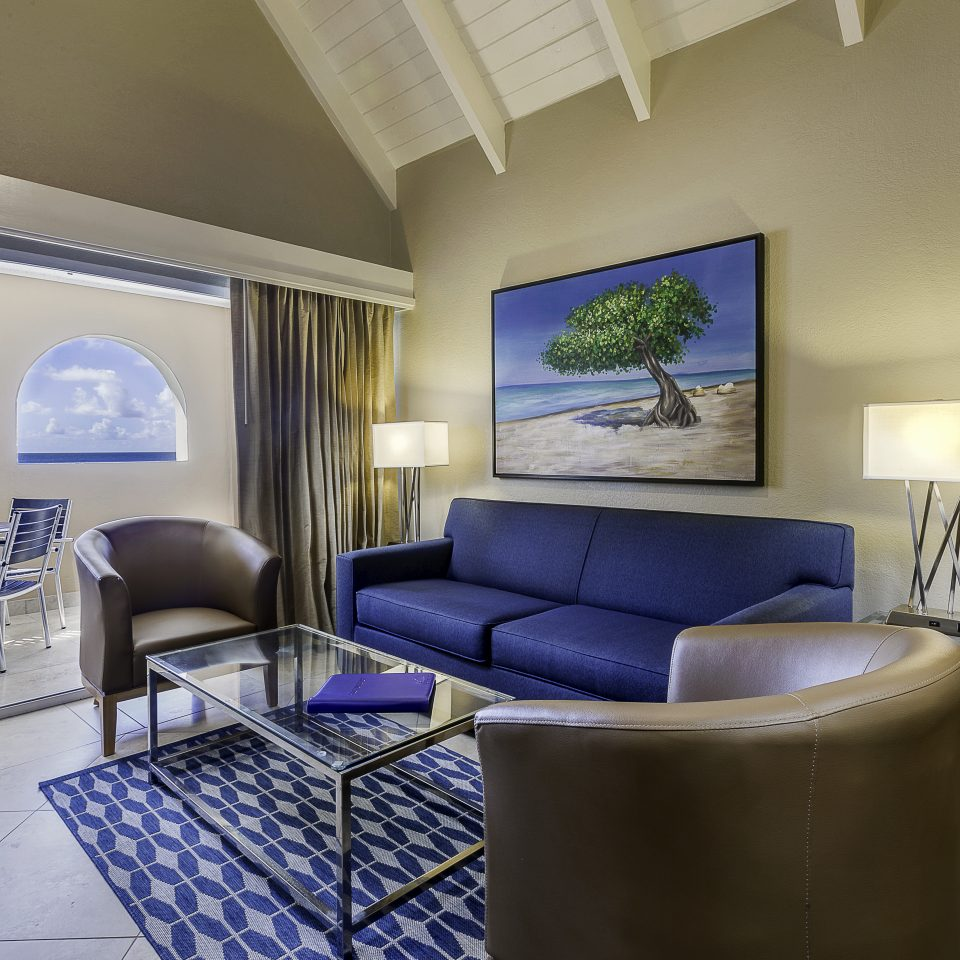 Living space in hotel room with dark blue accented furniture and decor along with outdoor closed balcony space