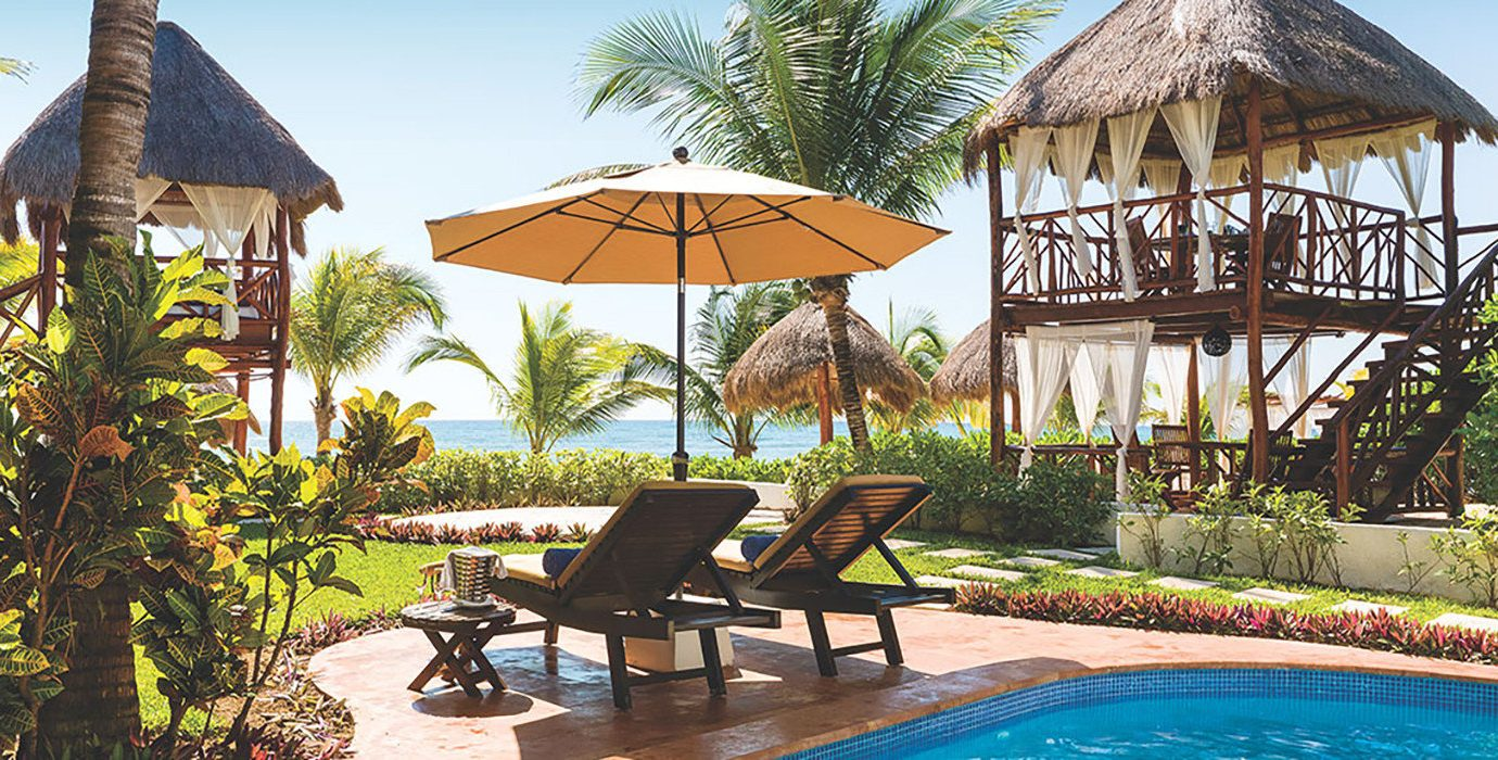 Hotels outdoor tree umbrella chair property Resort building leisure estate swimming pool real estate outdoor structure cottage lawn gazebo home backyard vacation Villa hacienda landscaping outdoor furniture lined set shade furniture several