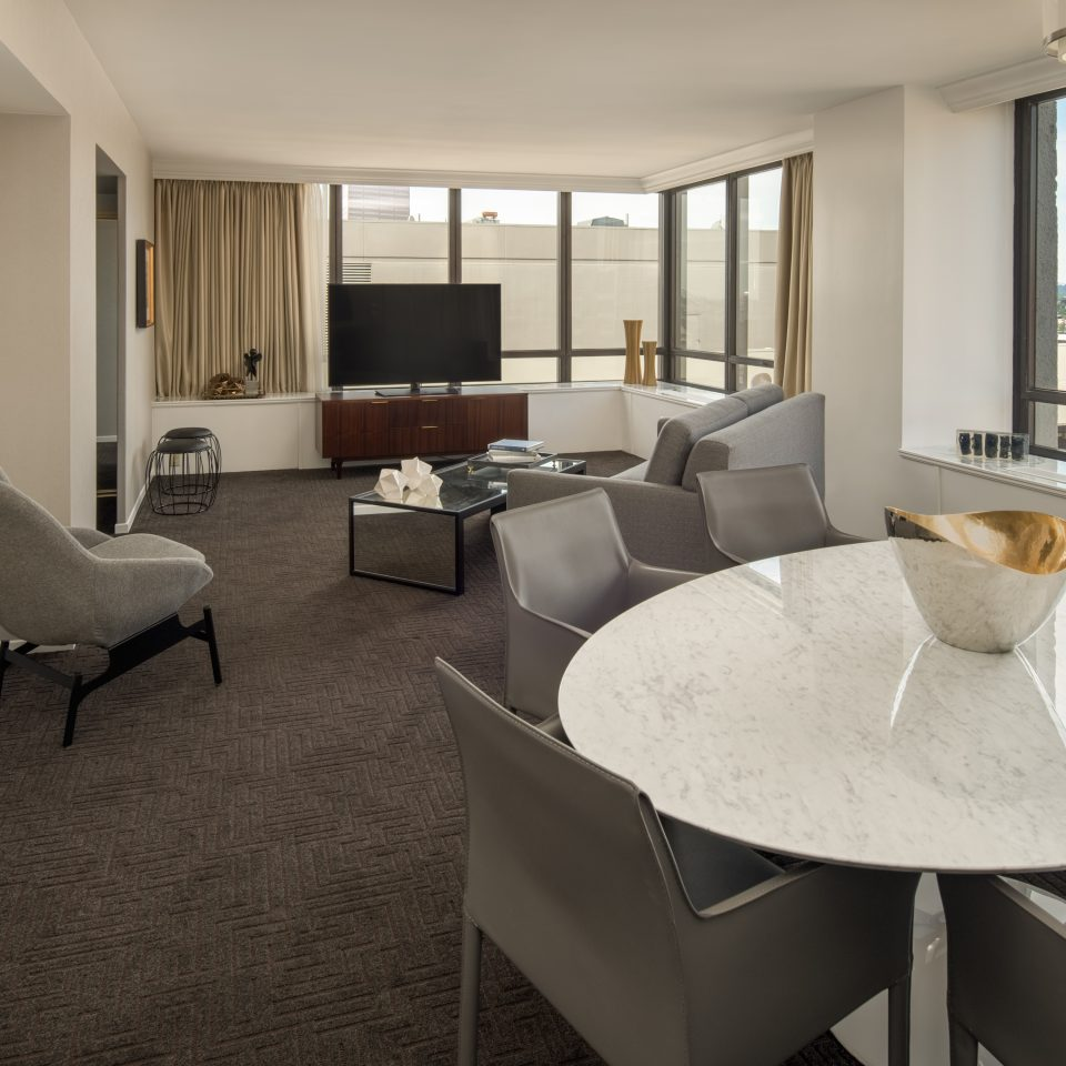 Suite showing TV, grey furniture, and round shiny white table
