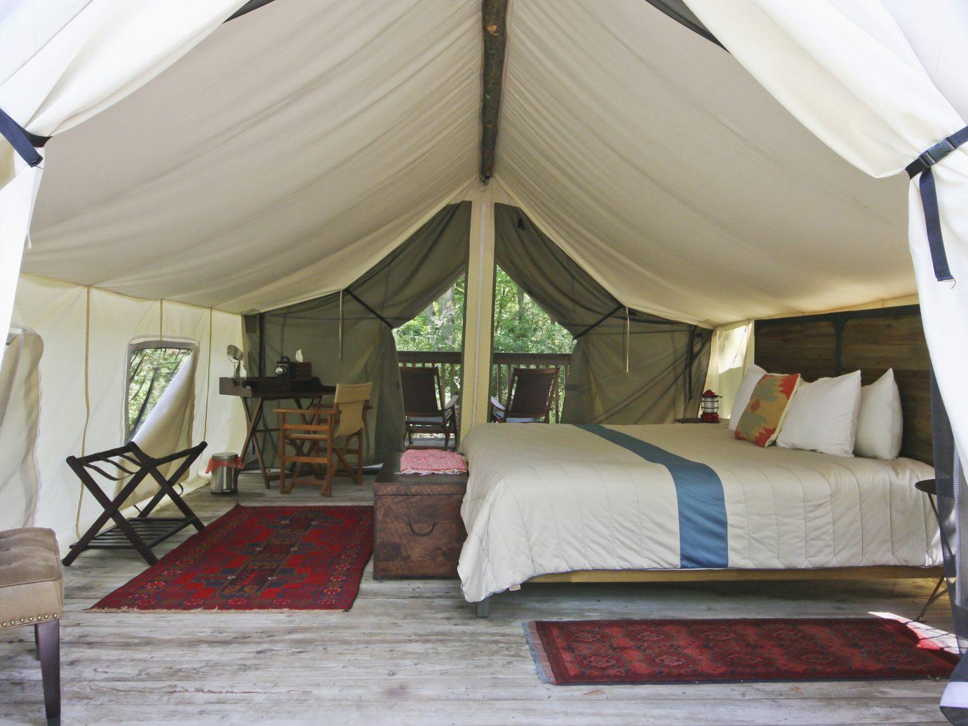 Glamping Outdoors + Adventure Weekend Getaways indoor floor tent room Bedroom camp estate outdoor object furniture