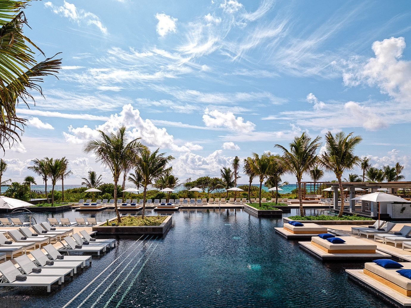 Boutique Hotels Hotels Luxury Travel sky outdoor water tree Boat Resort waterway swimming pool palm tree arecales leisure marina reflection dock vacation tropics real estate tourism docked estate resort town caribbean condominium Sea cloud hotel plant lined several