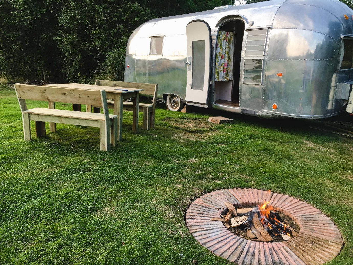 Glamping Outdoors + Adventure Trip Ideas grass outdoor tree camping vehicle travel trailer trailer park caravan motor vehicle automotive exterior recreation lawn plant community