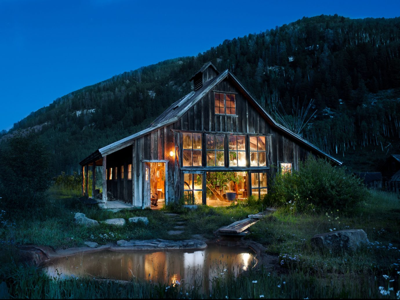 Boutique Hotels Fall Travel Hotels Outdoors + Adventure sky outdoor Nature reflection home building cottage house mountain hut log cabin evening rural area real estate mountain range landscape Winter farmhouse tree barn night computer wallpaper water estate hillside