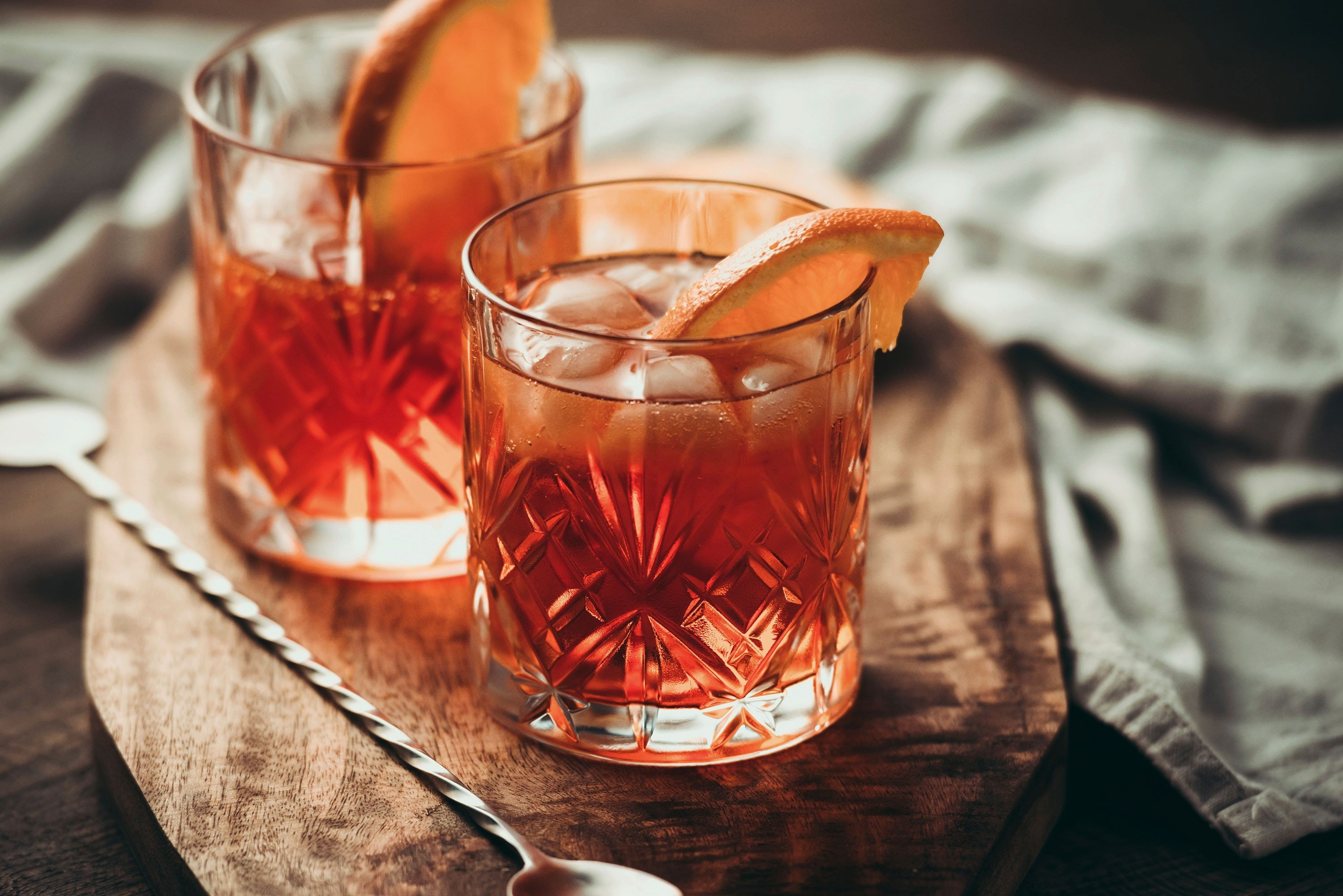 Food + Drink table cup sitting indoor Drink glass alcoholic beverage distilled beverage slice whisky negroni old fashioned container beverage alcohol close meal sliced