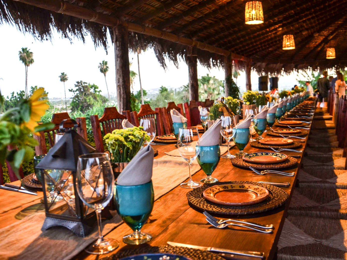 colorful Dining flowers Greenery isolation outdoor dining Outdoors private remote restaurant Rustic Scenic views table table setting thatched roof Travel Tips Trip Ideas view outdoor Resort meal tourism wooden estate wood furniture several dining table